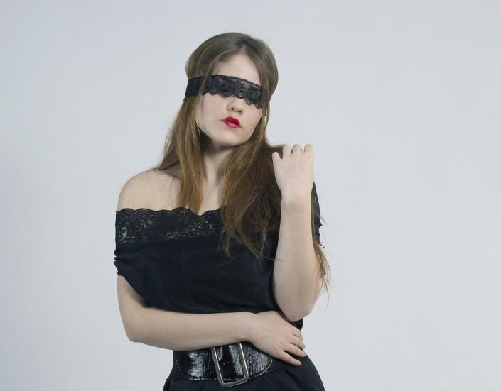 Hübsche Frau mit verbundenen Augen im schwarzen Kleid